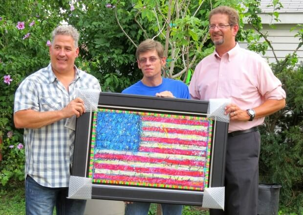 From left: Artist Tim Yanke, home recipient Michael Munger, CEO and executive director of HFHOC Tim Ruggles