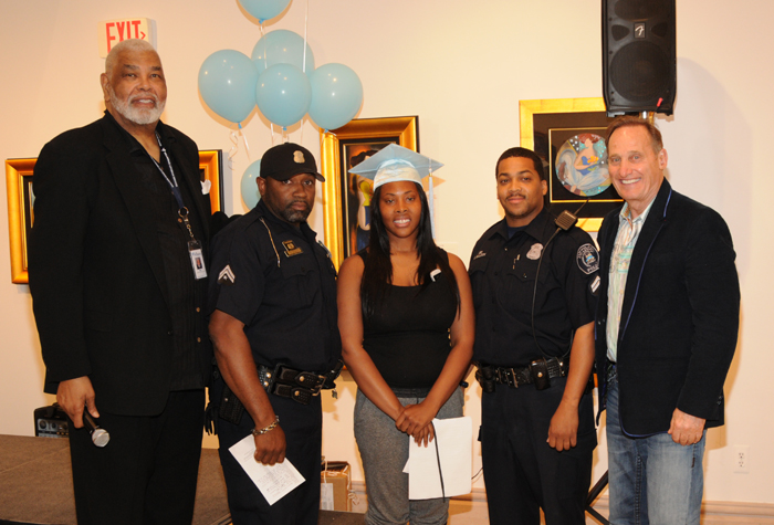 Former Piston's coach Ray Scott, Park West CEO and founder Albert Scaglione, adn two Detroit police officers presented graduate Christine Griffin with the Elaine Frinkley scholarship.