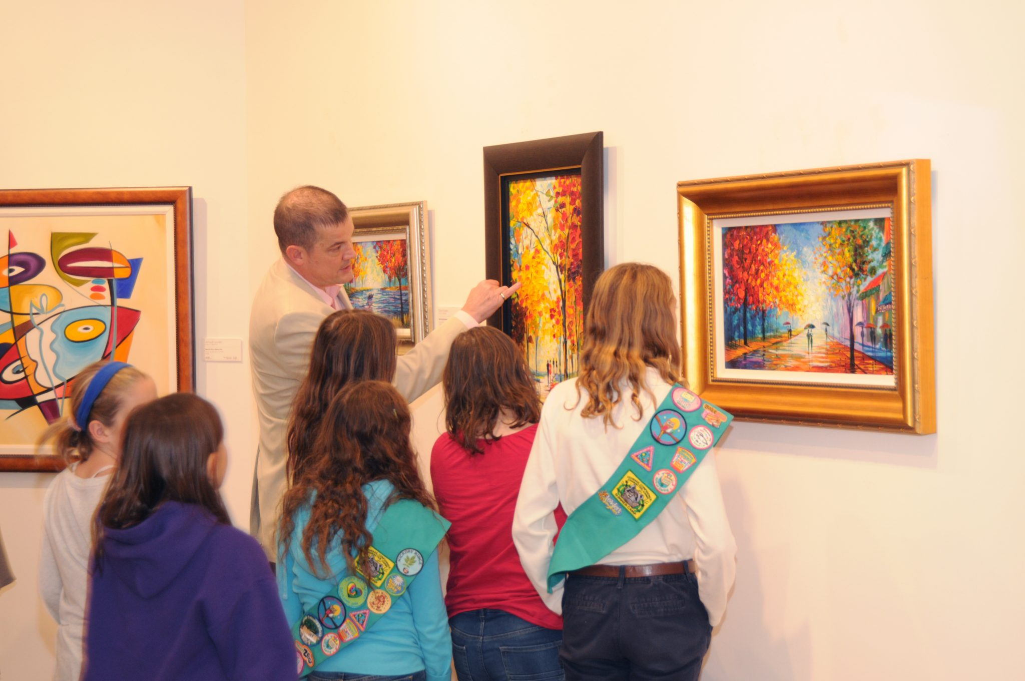 Girl Scouts learn about palette knife technique by studying a painting by Slava Ilyayev