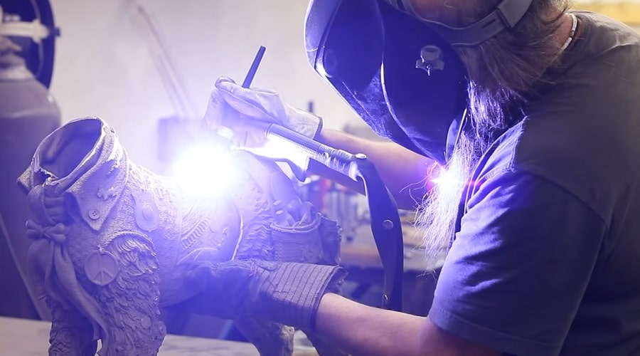 Lopez welds together the bronze pieces of one of his sculptures.