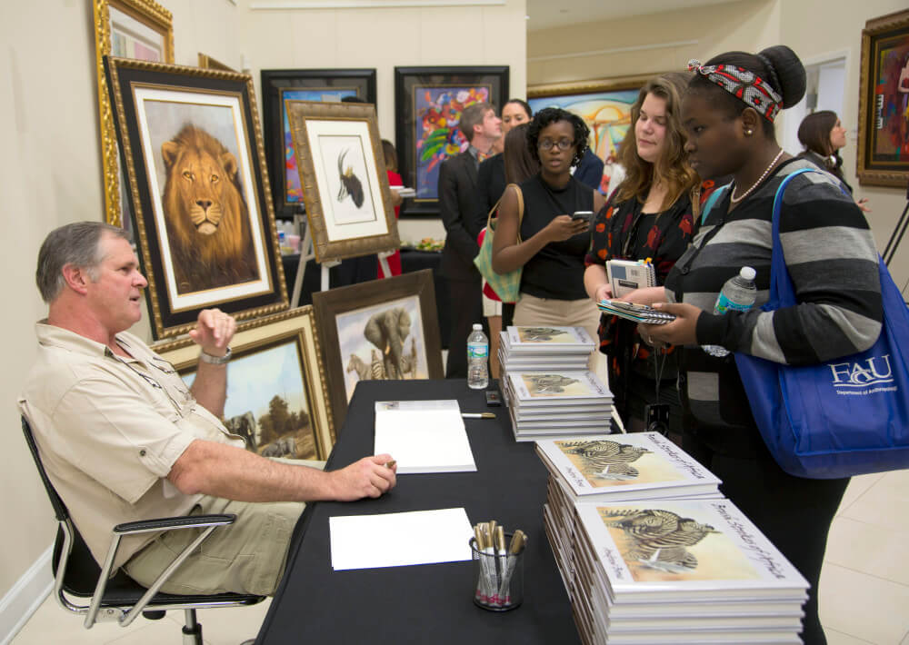 """Andrew Bone singing copies of his book """"Brush Strokes of Africa,"""" which collects examples of his breathtaking art and his memories of growing up in Zimbabwe."""