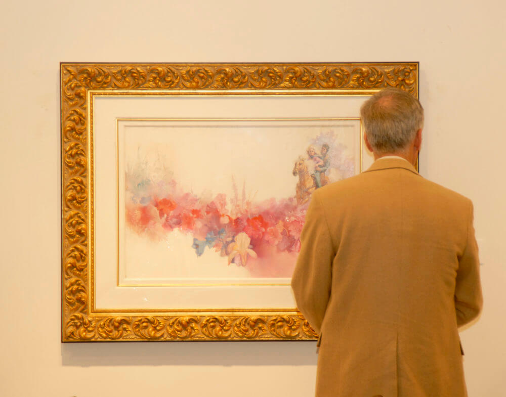 A collector views work by Pino at Park West Gallery.