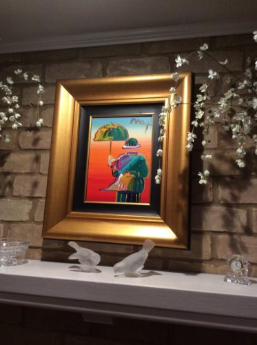 a Peter Max painting hung above a fireplace in a gold frame