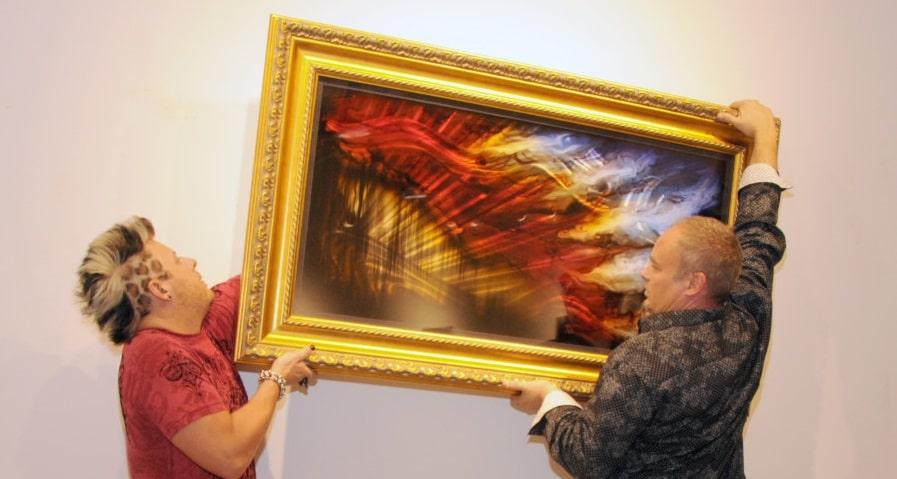 Chris DeRubeis and art publisher David Smith hanging metal art by DeRubeis.