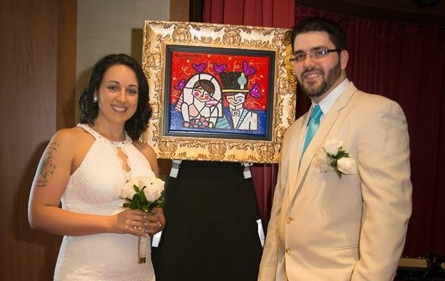 Carolyn and Christopher pose with their new Romero Britto painting at their cruise ship wedding.