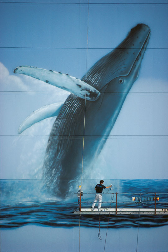"Wyland working on his sixth ""Whaling Wall"" mural, ""Hawaiian Humpbacks."" It was originally dedicated in Honolulu, Hawaii in 1985. (Image courtesy of the Wyland Foundation)"