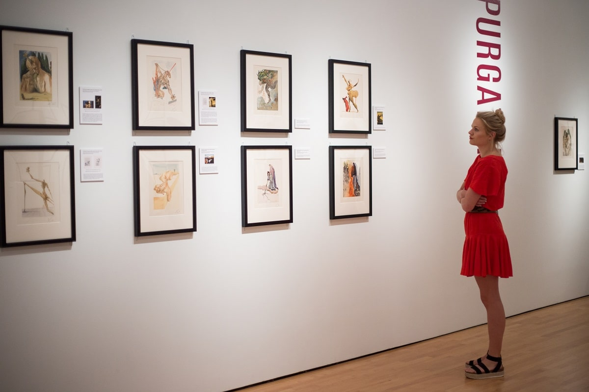 """A guest considers Dalí's take on Dante's """"Divine Comedy"""" at the Hilliard Art Museum's opening for """"Salvador Dalí's Stairway to Heaven."""""""