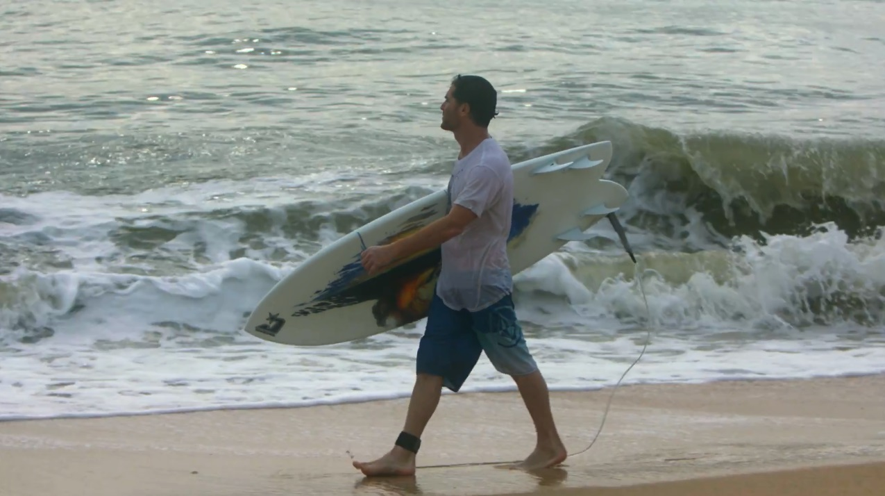 Artist Matt Beyrer walks in the surf.