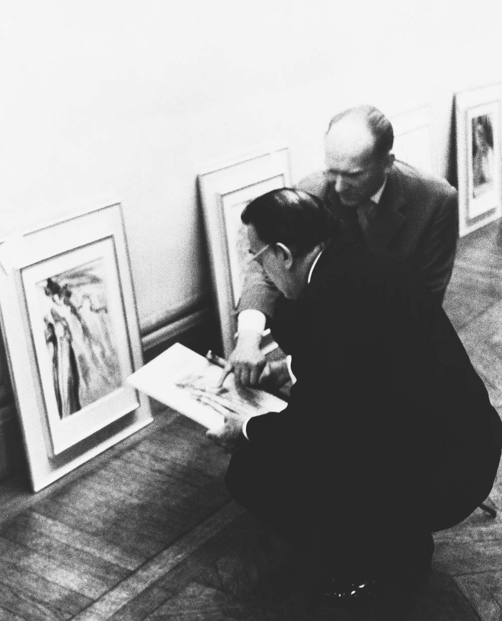 """Salvador Dalí and Jean Estrade examine wood engraving proofs for """"The Divine Comedy"""" during preparations for the exhibition of Dalí's """"Divine Comedy"""" watercolors at the Museum Galliera, Paris (May 19, 1960). (Photo credit: Eduard Fornés)"""