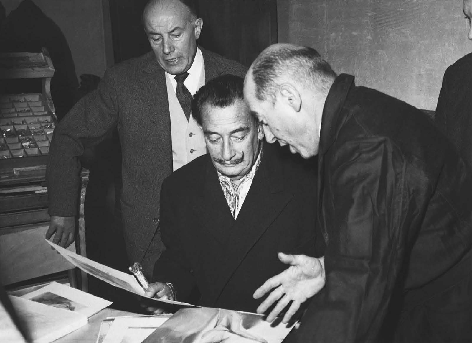 """Joseph Forêt, Salvador Dalí, and the engraver, Raymond Jacquet, examining one of the engravings from """"The Divine Comedy."""" (Photo credit: Eduard Fornés)"""