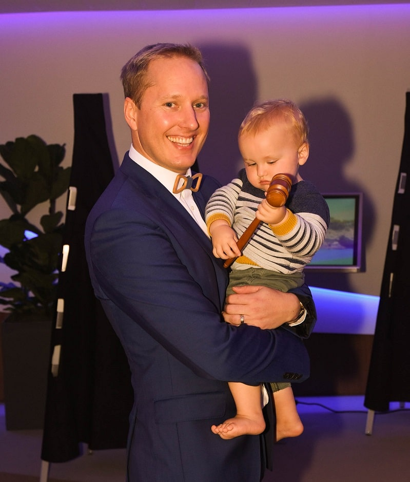 Auctioneer Deon van der Merwe teaches his son how to use a gavel on Celebrity Edge.