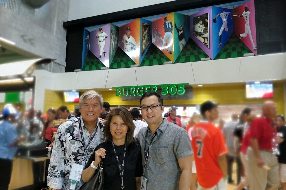 """The Pangborn family posing in front of Dominic's """"Art in Motion"""" at Marlins Park."""