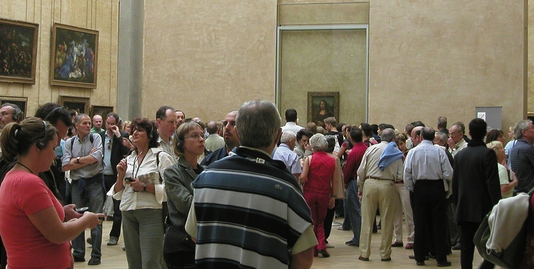 """Crowds navigate the """"Mona Lisa"""" gallery at the Louvre"""