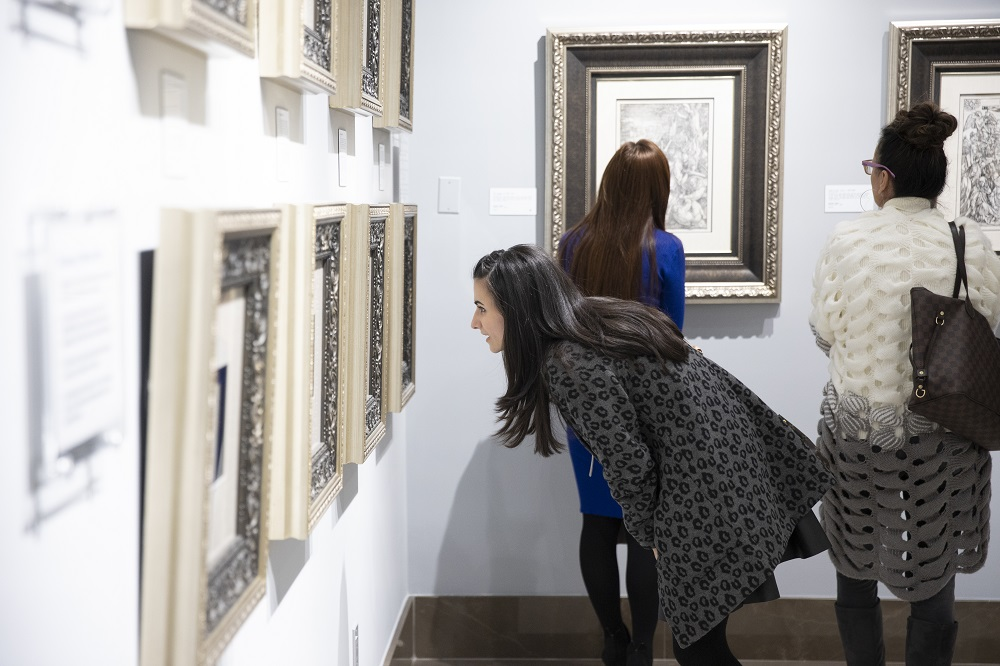 A curious patron takes an up-close look at an etching by Rembrandt van Rijn.