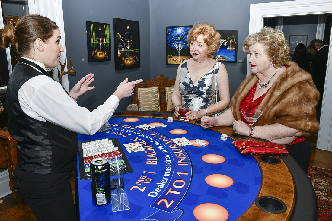 Two Monthaven patrons place their bets while surrounded by Michael Godard's artwork.