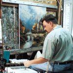 "Thomas Kinkade working on his acclaimed painting ""Mountain Chapel"""