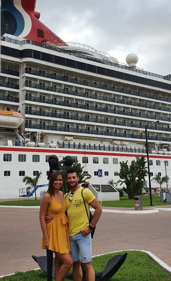 Nikki and her partner pose in front of one of the cruise ships where she works as an auctioneer.