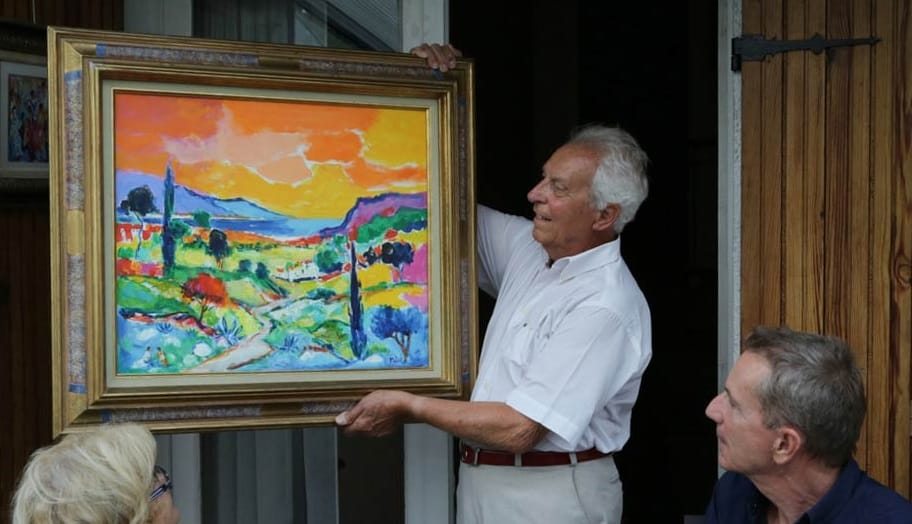 Jean-Claude Picot proudly shows one of his paintings at his home in France.