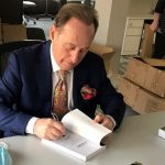 """Albert Scaglione signing copies of """"The Book of Albert"""" at the Park West Foundation in Michigan."""